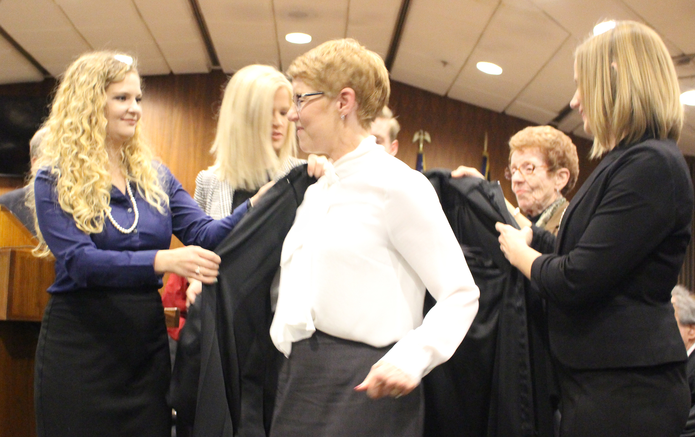 "Douglas County Juvenile Court Judge Mary ""Peg"" M.Z. Stevens puts on her robe with assistance from her children during an investiture ceremony in the Legislative Chambers of the Omaha-Douglas County Civic Center on Friday, Jan. 3, 2020. (Photo by Scott Stewart)"