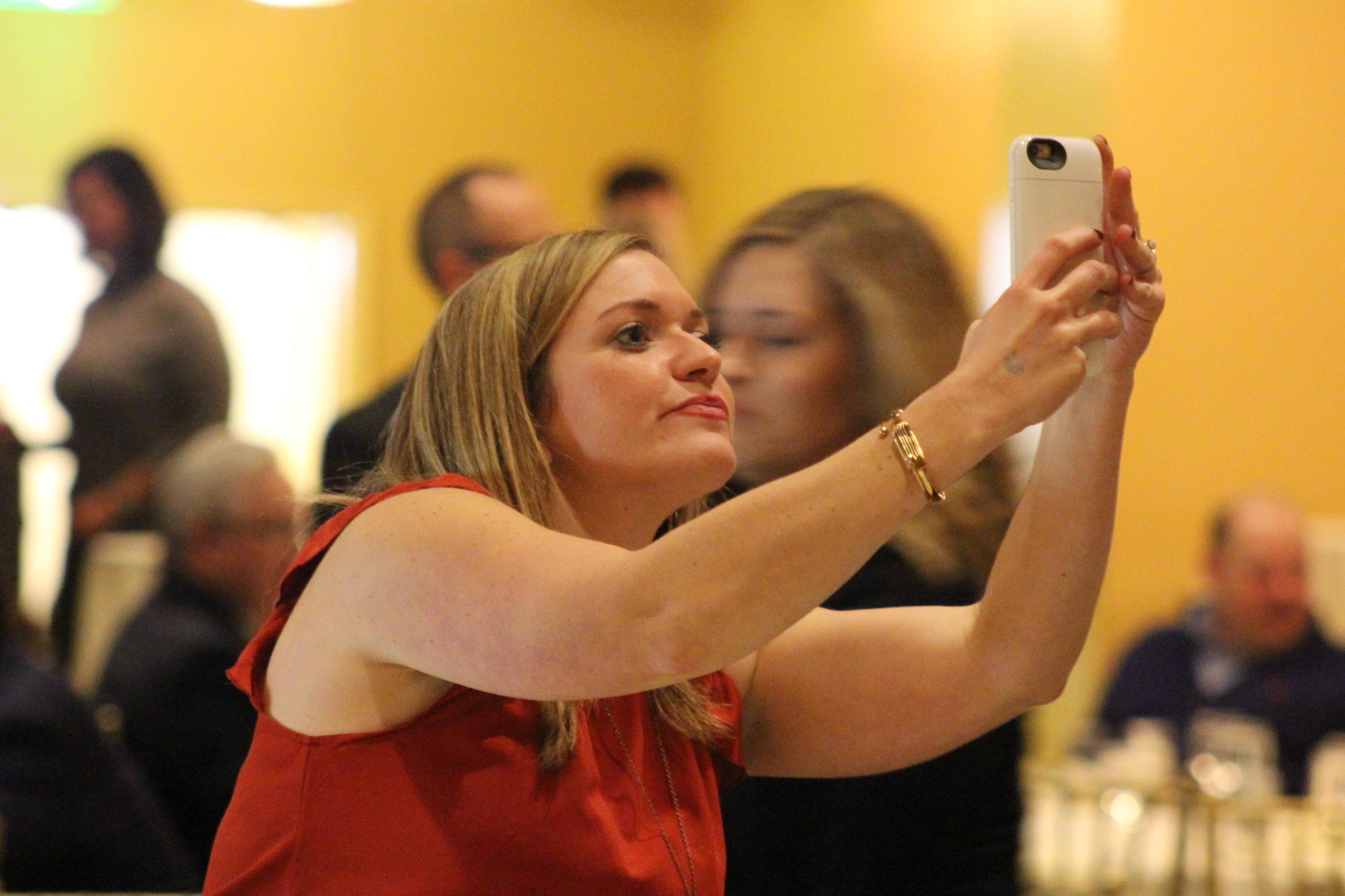 Christine Mori of the Douglas County Public Defender's Office snaps a photo before the start of the Barristers' Club Christmas show at the Paxton Ballroom, 1403 Farnam St., on Dec. 12, 2019. (Photo by Scott Stewart)