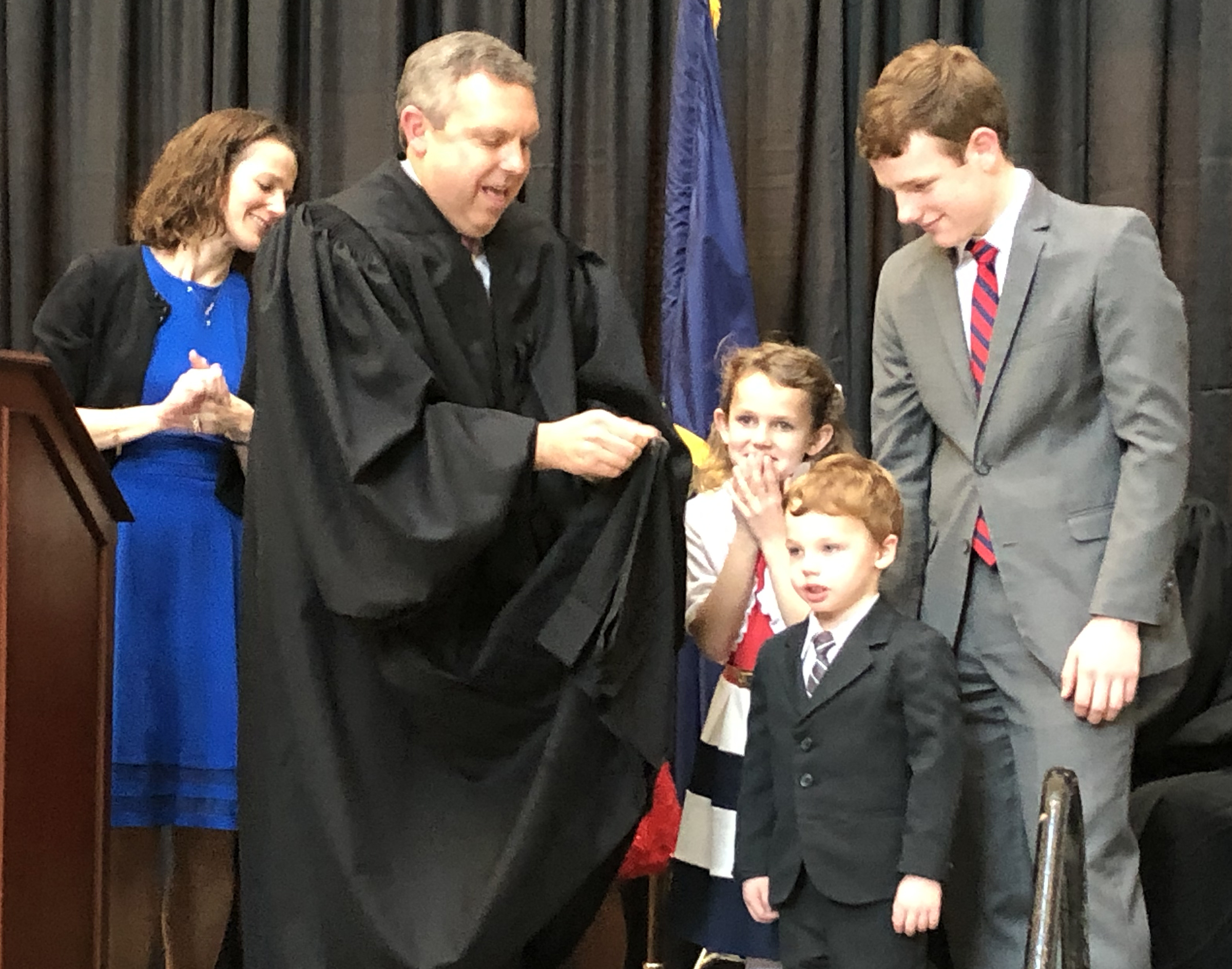 Brian C. Buescher dons his black robes with the help of his family during his investiture ceremony at the Hruska Federal Courthouse on Friday, Nov. 15, 2019. (Photo by Scott Stewart)