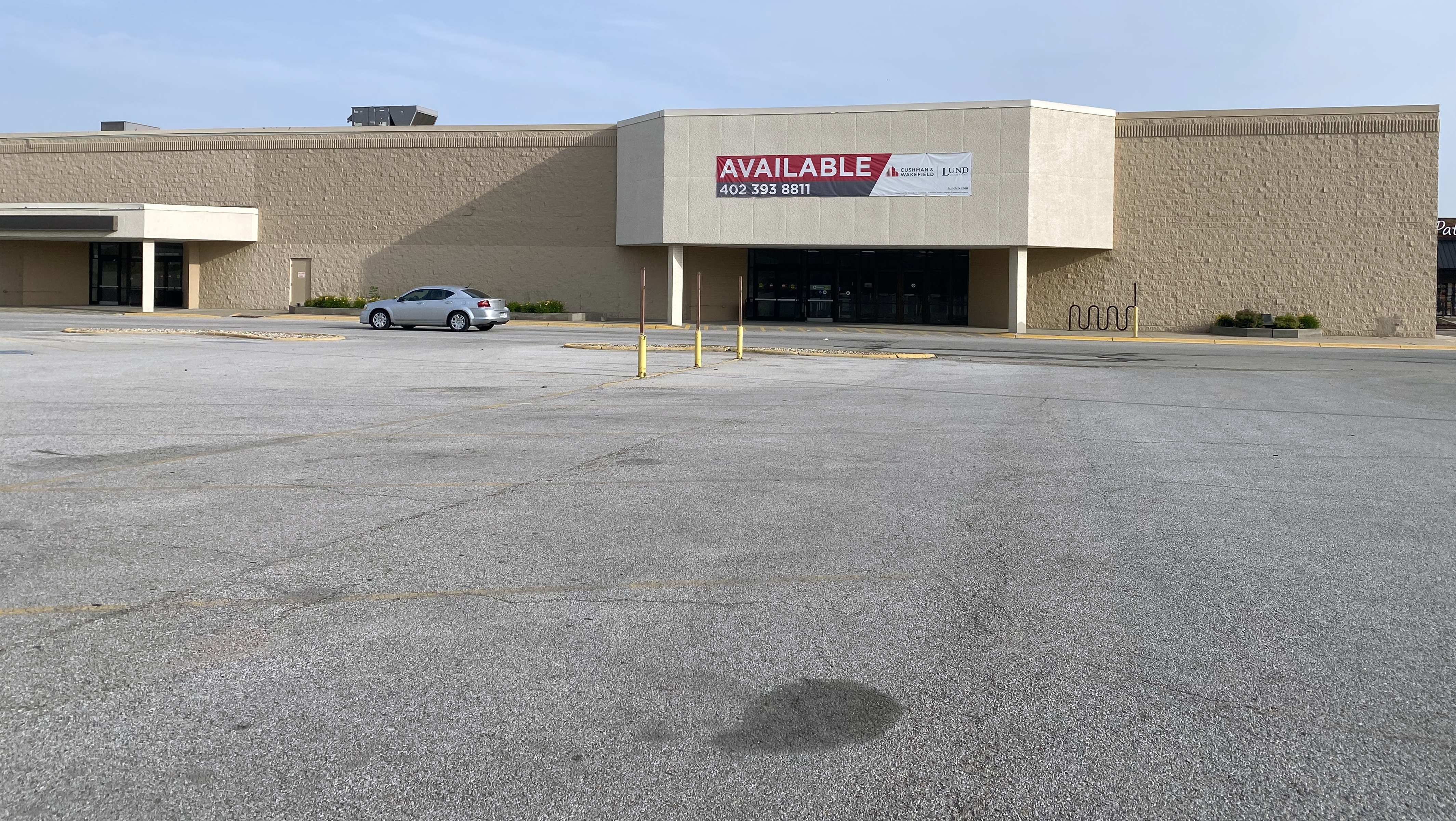 Above, a car drives by a former Shopko store at 14445 W. Center Road that is listed for sale Sunday, June 28, 2020. Across the country, such signs are expected to be seen more frequently as the real estate industry struggles. (Scott Stewart)