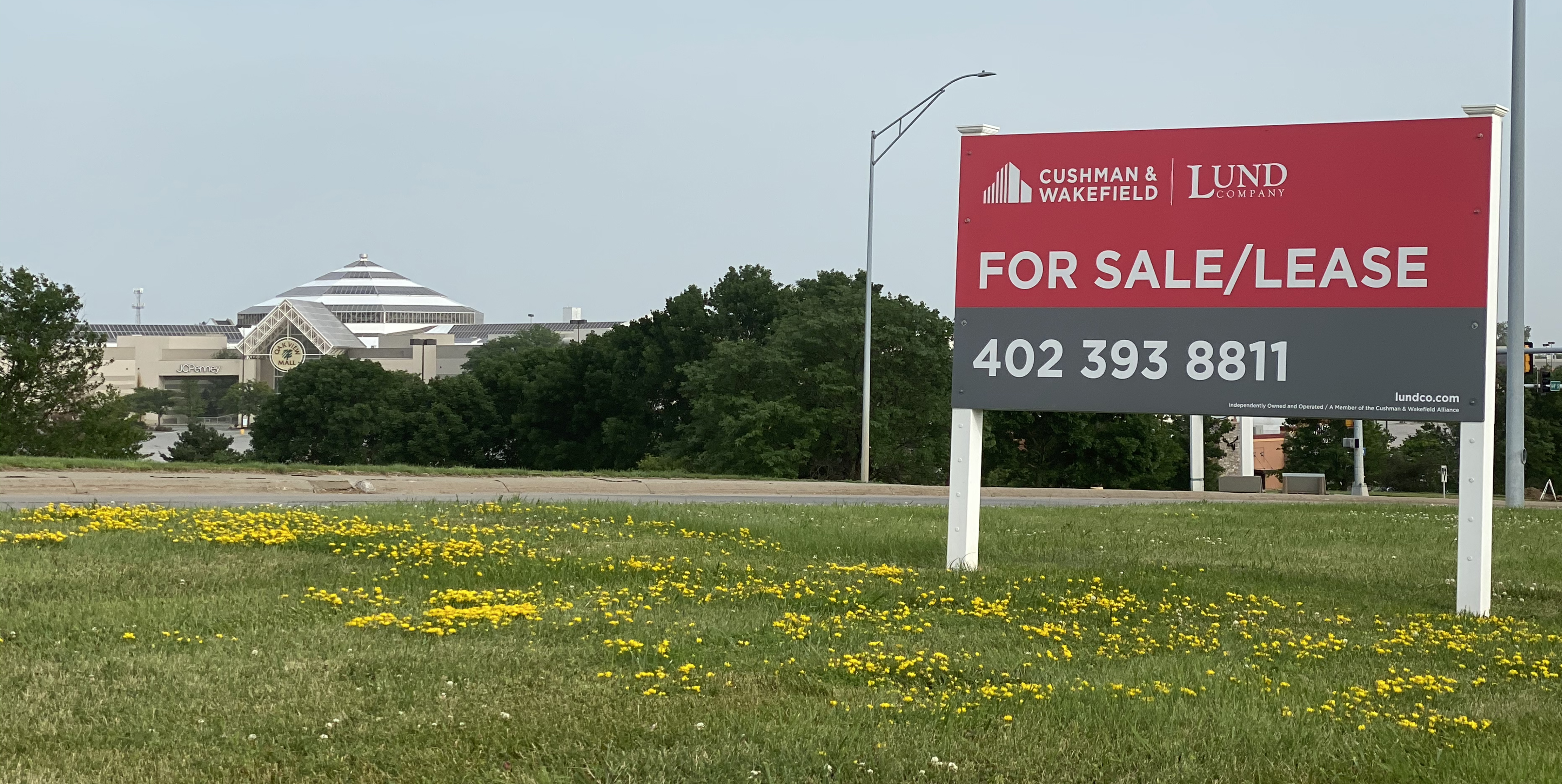 At right, a for sale or lease sign sits outside the Shopko property with Oakview Mall in the distance, which has other commercial real estate properties available for redevelopment. (Scott Stewart)