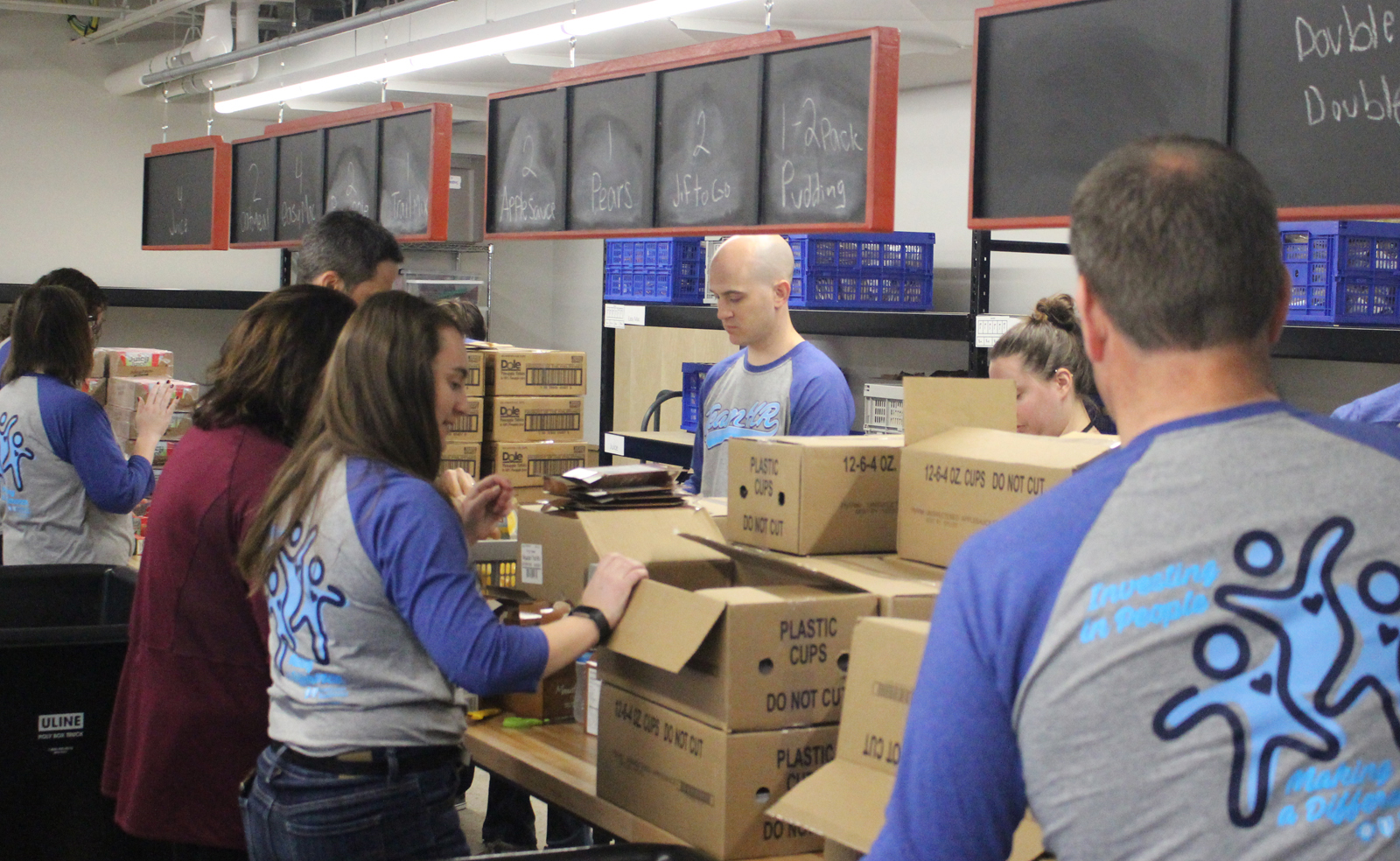 Volunteers unload food from Hy-Vee to prepare for the Completely KIDS weekend backpack program at the nonprofit's headquarters, 2566 St. Mary's Ave., on Tuesday, May 15, 2019. (Photo by Scott Stewart)