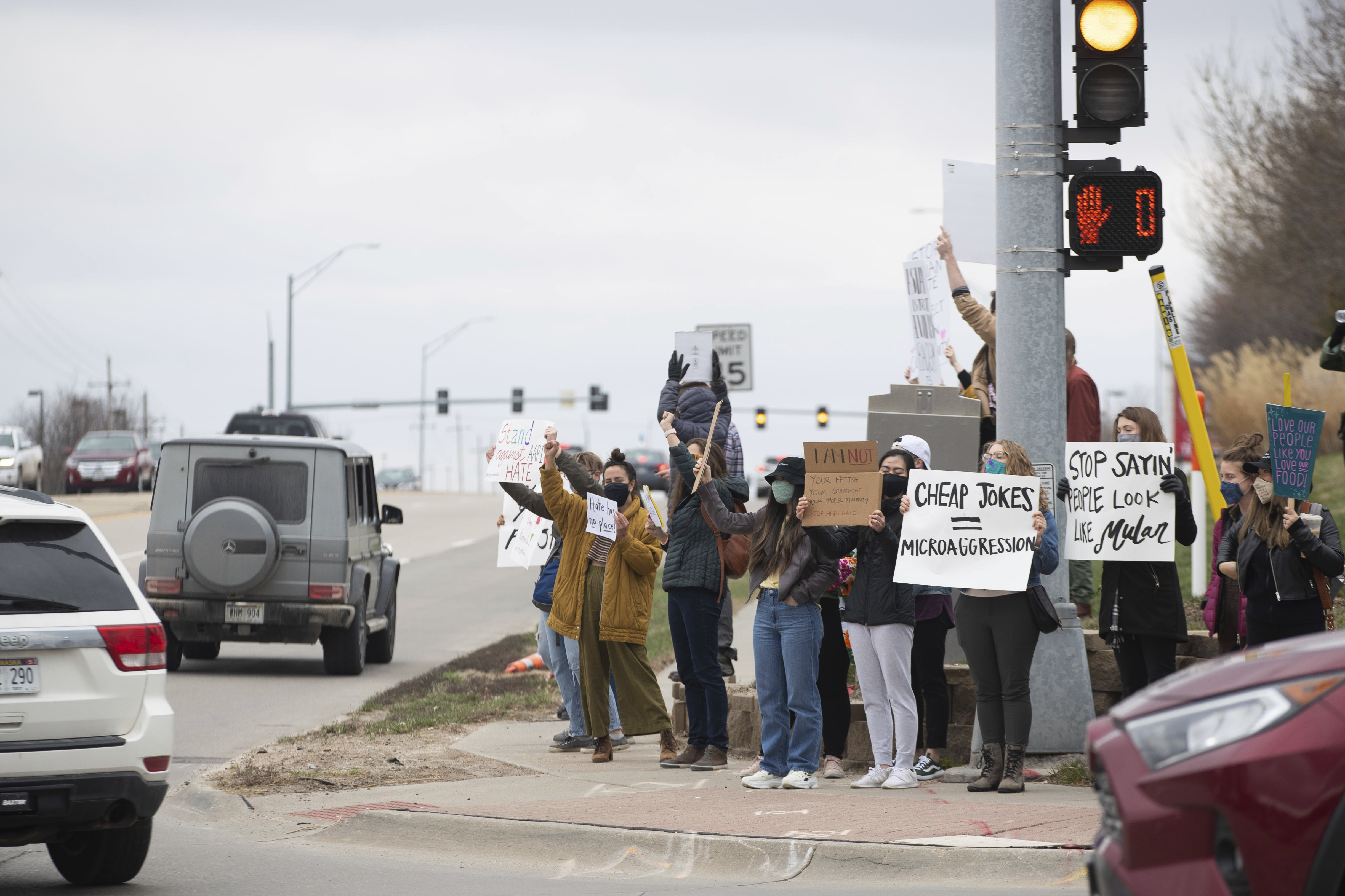 Community members hold up signs along 175th and West Center Road during a Stop Asian Hate rally in Omaha, March 27, 2021. (Lilly Smith/Omaha World-Herald via AP)