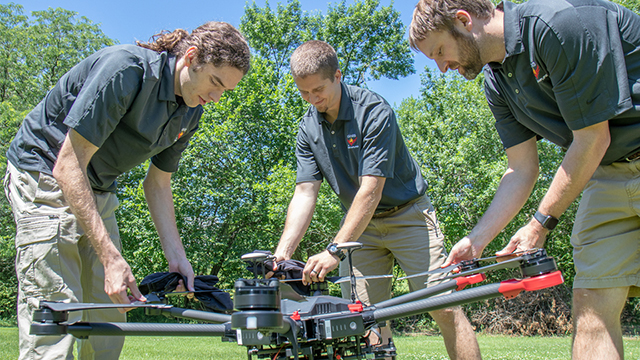 From left, Evan Beachly, Jim Higgins and Carrick Detweiler assemble a drone system before taking it for a test flight. The system features a software application that makes it easy to operate. It can also be flown at night, helping crews safely fight fires despite limited visibility. (Courtesy Alyssa Amen/NUtech Ventures/UNL)