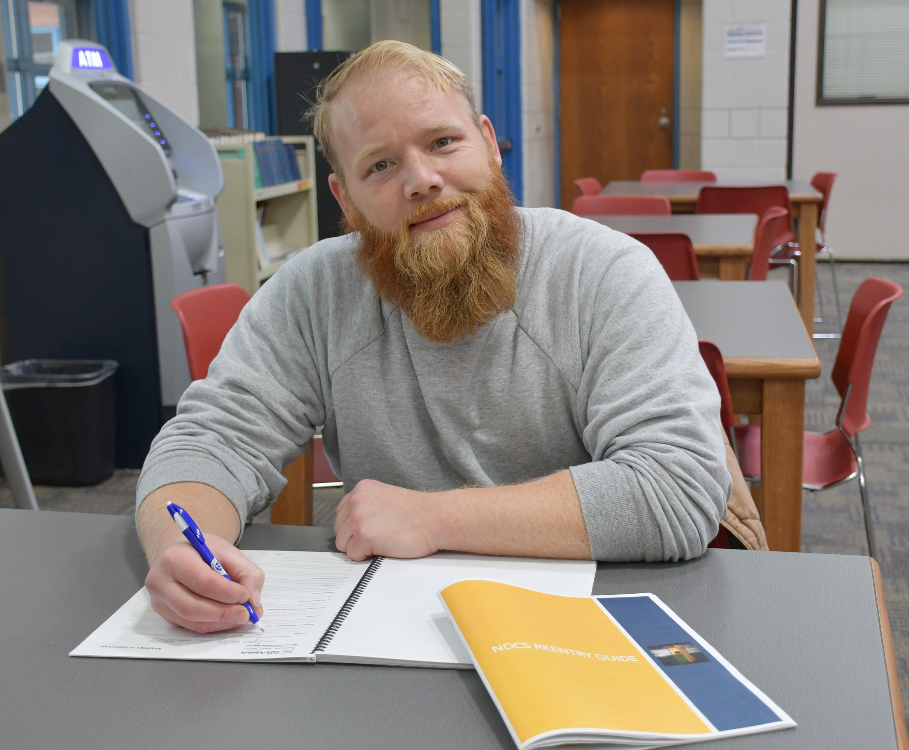 """Ryan Leiting writes in a workbook at Community Corrections Center-Lincoln. """"Reentry gives us hope for the future,"""" he said. """"These guides and workbooks give us that opportunity."""" (Courtesy NDCS)"""
