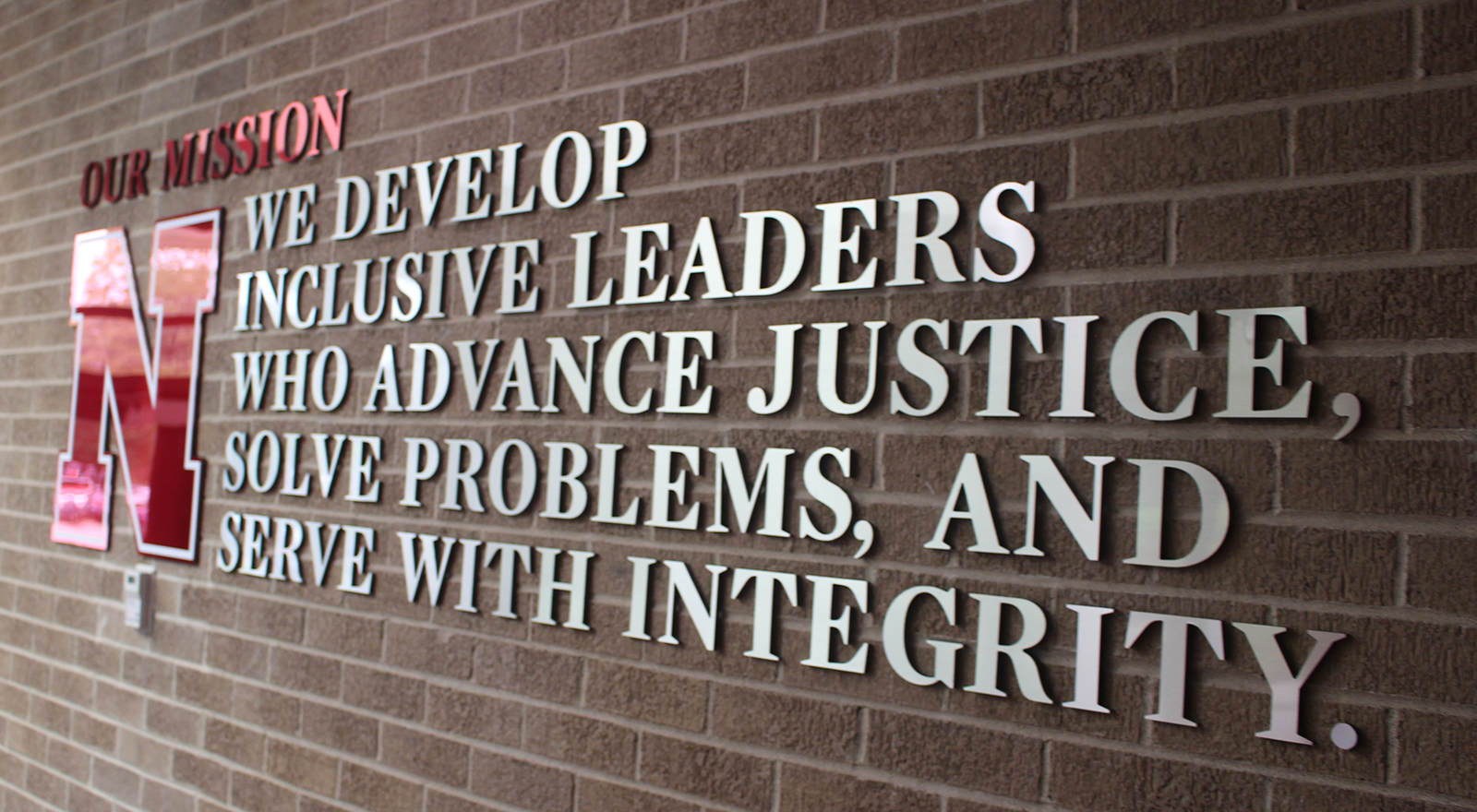 The new mission statement for Nebraska Law hangs by the entrance to McCollum Hall. (Photo by Scott Stewart)