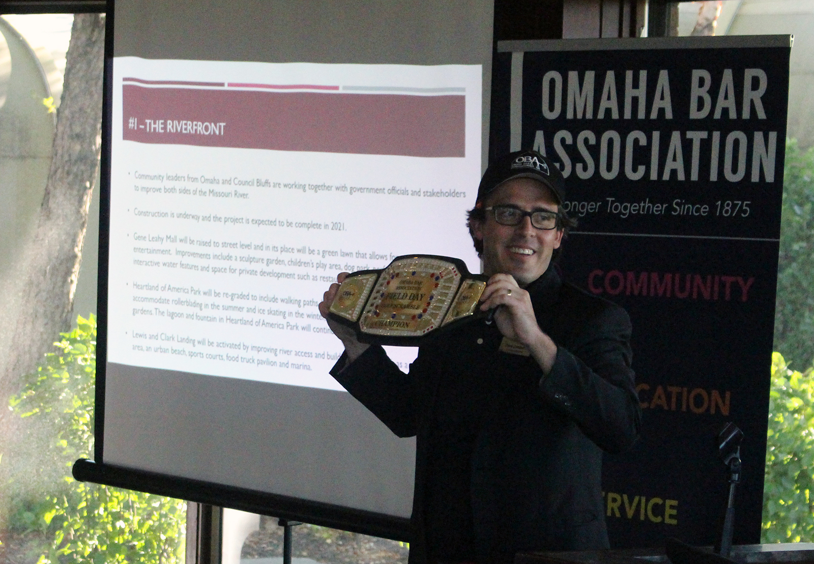 Dave Sommers, executive director of the Omaha Bar Associa-tion, holds up the champions belt for the OBA Field Day golf tournament during an awards presentation Monday at Cham-pions Run. (Photo by Scott Stewart)