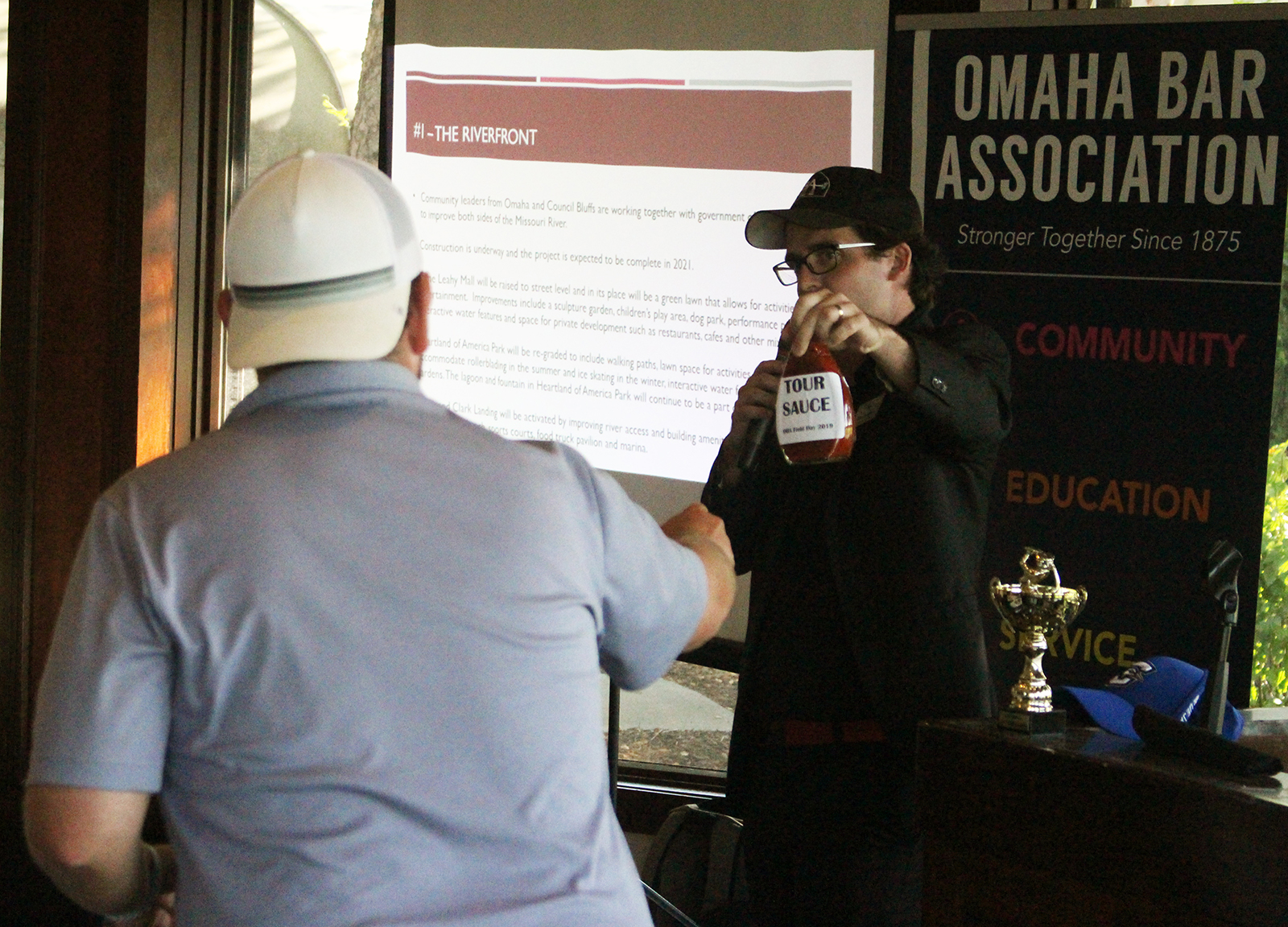 "Dave Sommers, executive director of the Omaha Bar Association, presents Patrick McNamara with the ""tour sauce"" award for having the je ne sais quoi of a professional golfer with a less-than-pro average. (Photo by Scott Stewart)"
