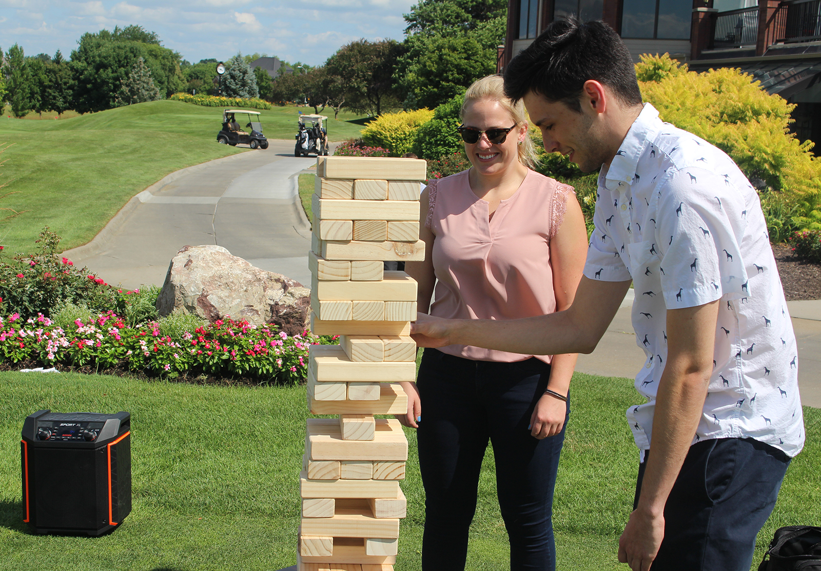 Connor Christensen pulls a brick from an outdoor Jenga set while Amelia Prickett watches during the field games competition at the Omaha Bar Association Field Day last Monday at Champions Run. Christensen and Prickett work for Warren Distribution. (Photo by Scott Stewart)