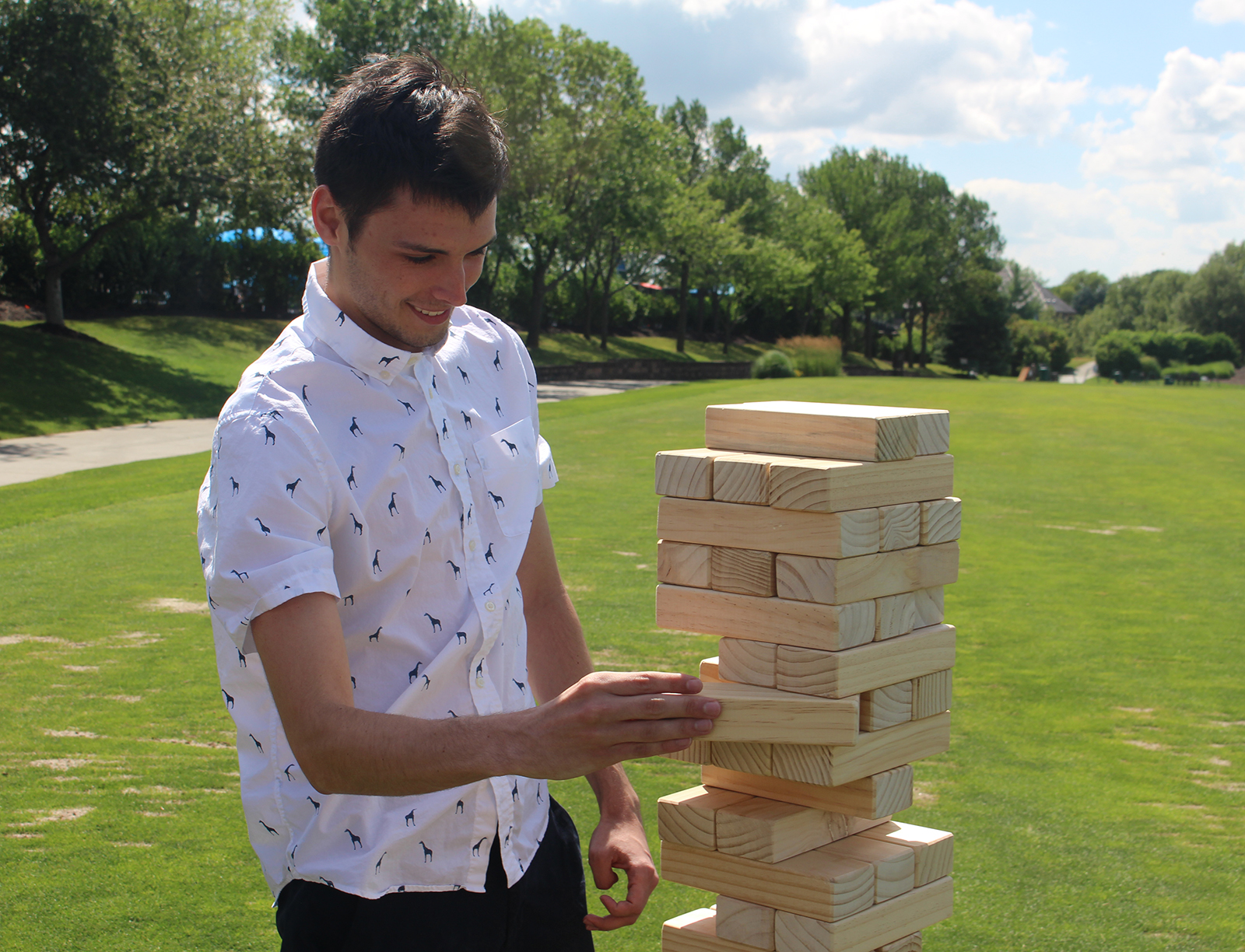 Connor Christensen of Warren Distribution pulls a brick from an outdoor Jenga set during the field games competition at the Omaha Bar Association Field Day last Monday at Champions Run. (Photo by Scott Stewart)