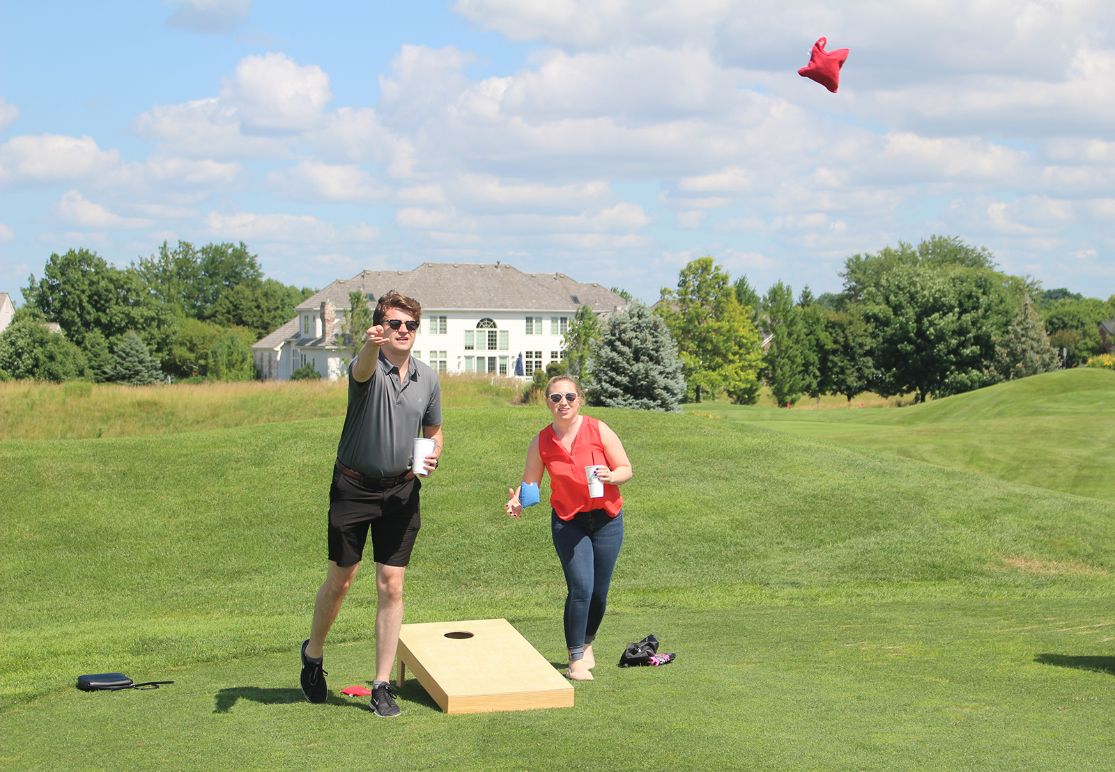 Stevie Chesterman, right, looks on while Cole Burmeister tosses a bean bag during a game of cornhole Monday at the Omaha Bar Association Field Day at Champions Run. They both work at the Sarpy County Public Defender's Office. (Photo by Scott Stewart)