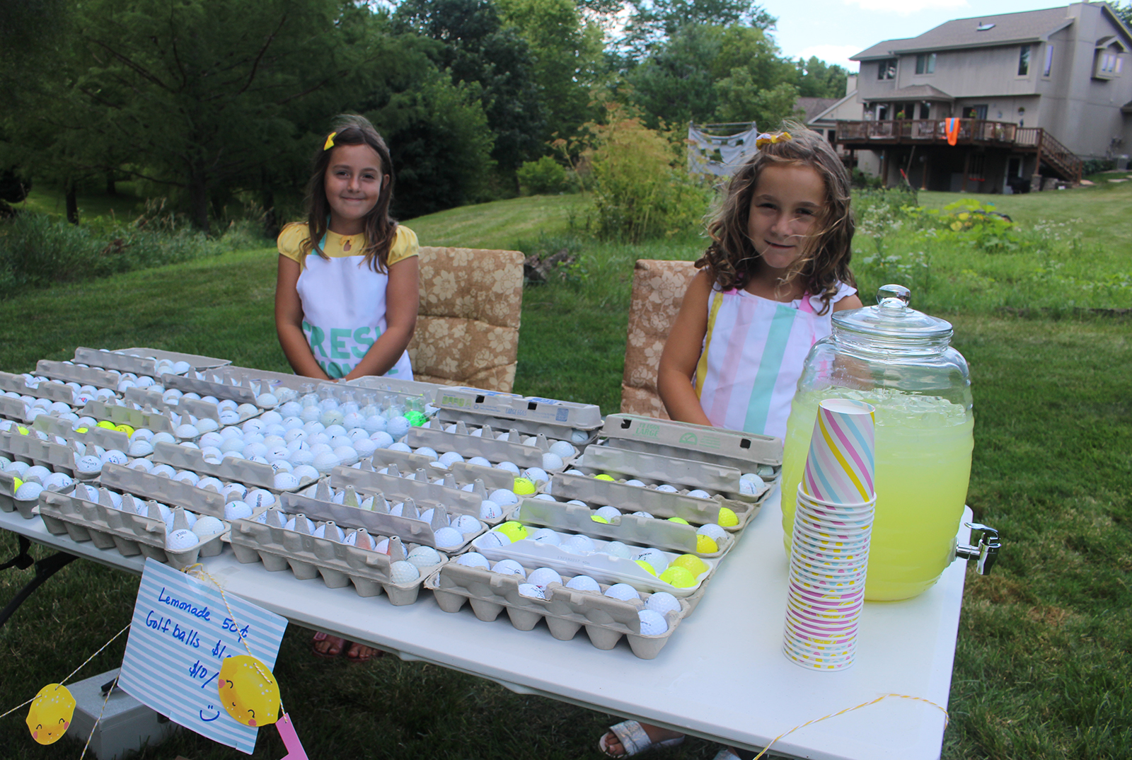 Hazel Wignall, left, and her twin sister Olive sell golf balls and lemonade from a stand in their back yard, which abuts Champions Run, on Monday during the Omaha Bar Association Field Day. (Photo by Scott Stewart)