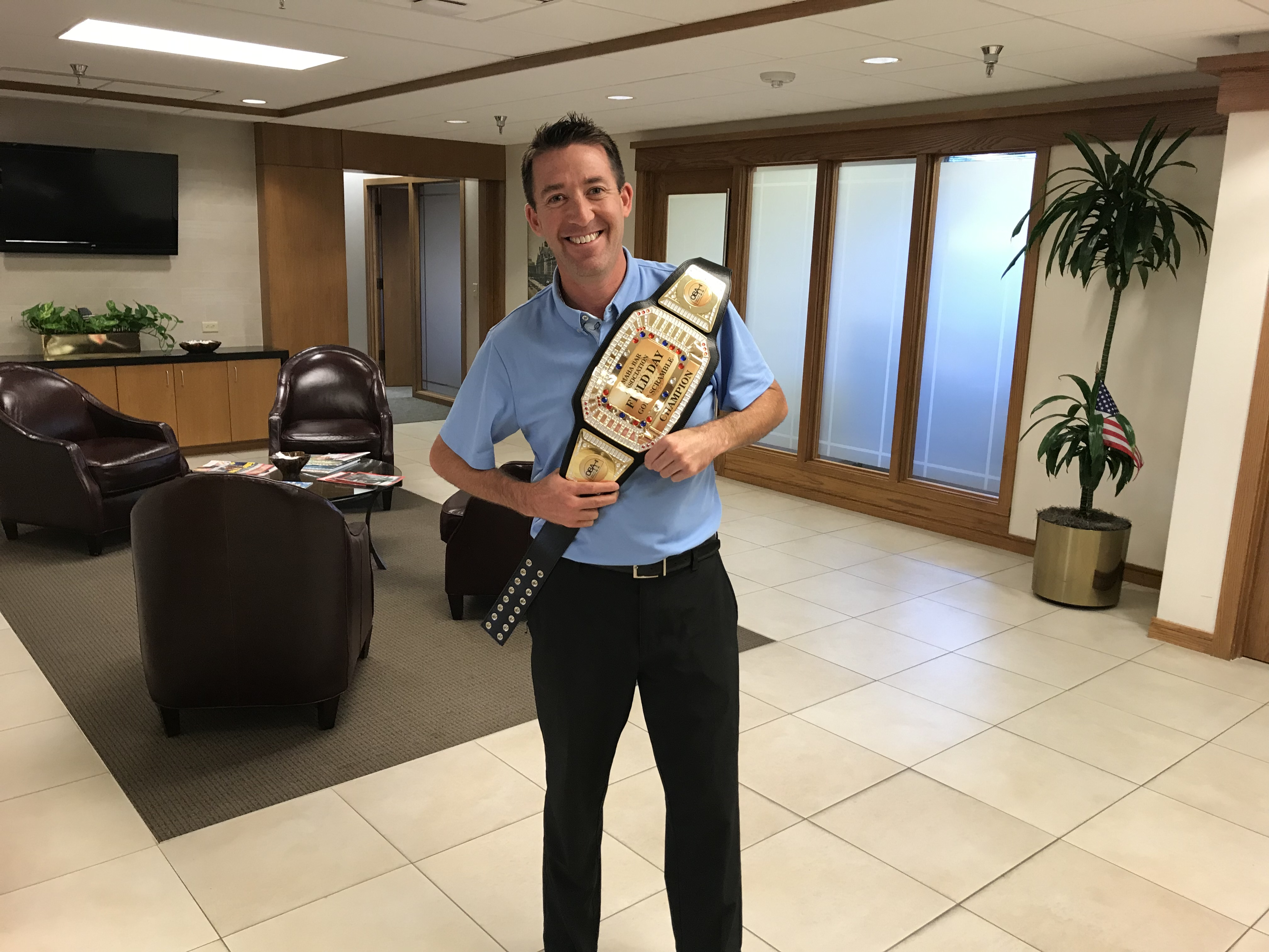 Shay Garvin accepted the Omaha Bar Association Field Day golf championship belt on Tuesday, July 23. He accepted the award on behalf of an Erickson | Sederstrom foursome that couldn't stay for Mon-day's dinner. (Courtesy Dave Sommers)