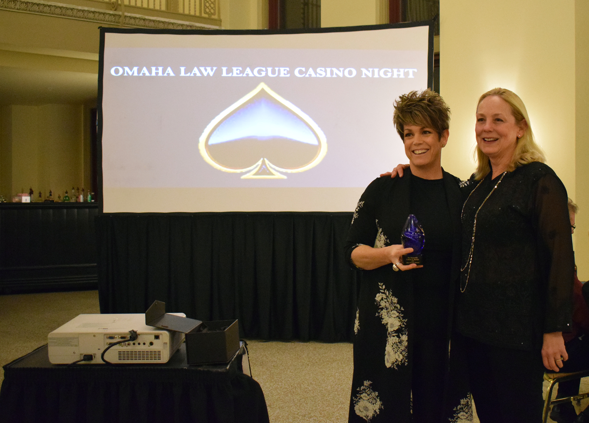 Kathy Knickrehm, right, receives a service award for her dedication to the Omaha Law League from Douglas County Court Judge Marcela Keim at the OLL Casino Night at the Livestock Exchange Building on March 6, 2020. (Photo by Elizabeth A. Elliott)