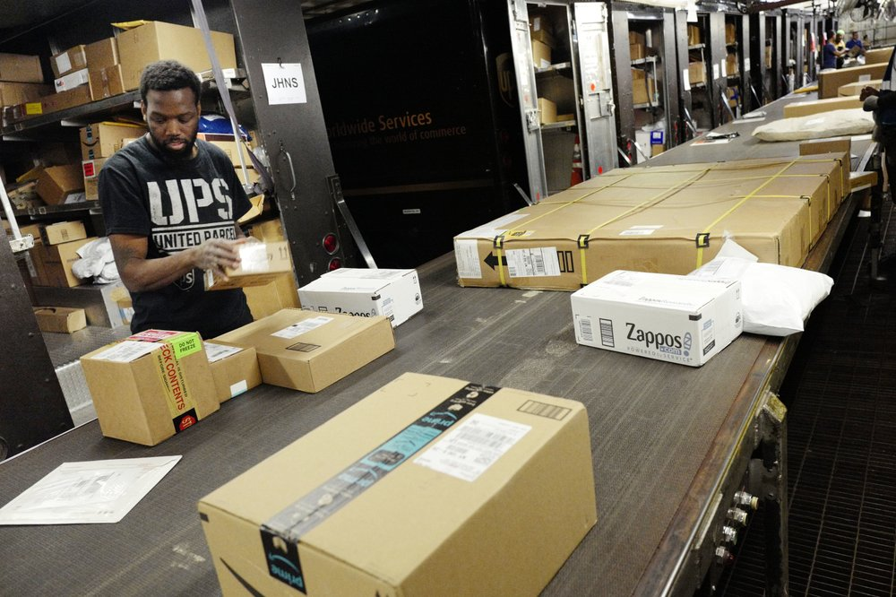 A UPS employee takes packages from a conveyor belt for loading onto a truck at a UPS facility in New York, May 9, 2017. Carriers like FedEx and UPS have been ramping up their holiday hiring while asking store clients to move their shipping volume on lighter days in their network. Stores are also pushing their customers to buy early to smooth out the peaks in the weeks leading up to Christmas. (AP)