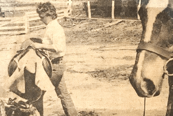 Judge Sylvia H. Rambo was an avid horse rider for many years. In this 1980 photo, taken at her farm in Pennsylvania, she removes a saddle from her horse, Joy. (Courtesy Sylvia Rambo via U.S. Courts)