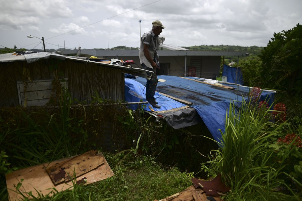 Wilfredo Negron stands on the rooftop of one of his properties securing the zinc roof in preparation for the current hurricane season, in Corozal, Puerto Rico, Monday, July 13, 2020. Many people face a new hurricane season under fading blue tarp roofs and the latest program to solve the housing crisis hasn't yet finished a single home. (AP)
