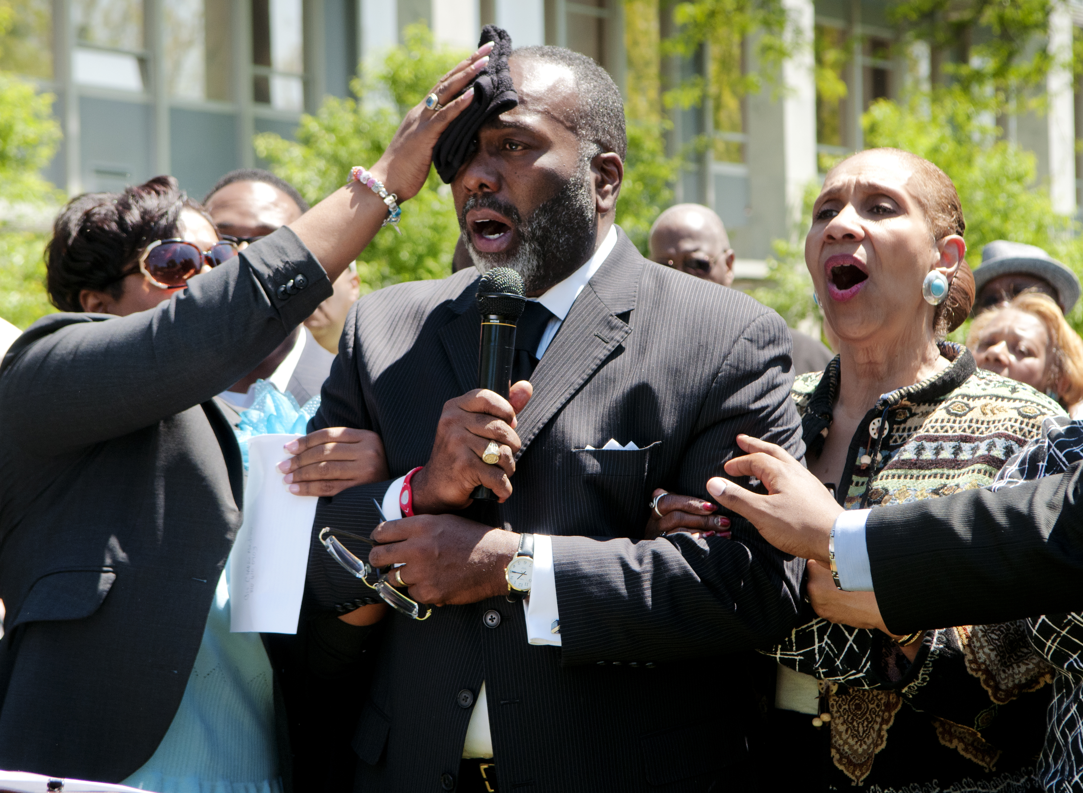 """Delores Flynn wipes the forehead of her husband, Rev. Reginald Flynn, as he leads a crowd gathered on the front lawn of City Hall in Flint, Mich., in singing """"We Shall Overcome"""" at the end of a rally against Public Act 4, May 14, 2012. (Ryan Garza/Flint Journal via AP)"""
