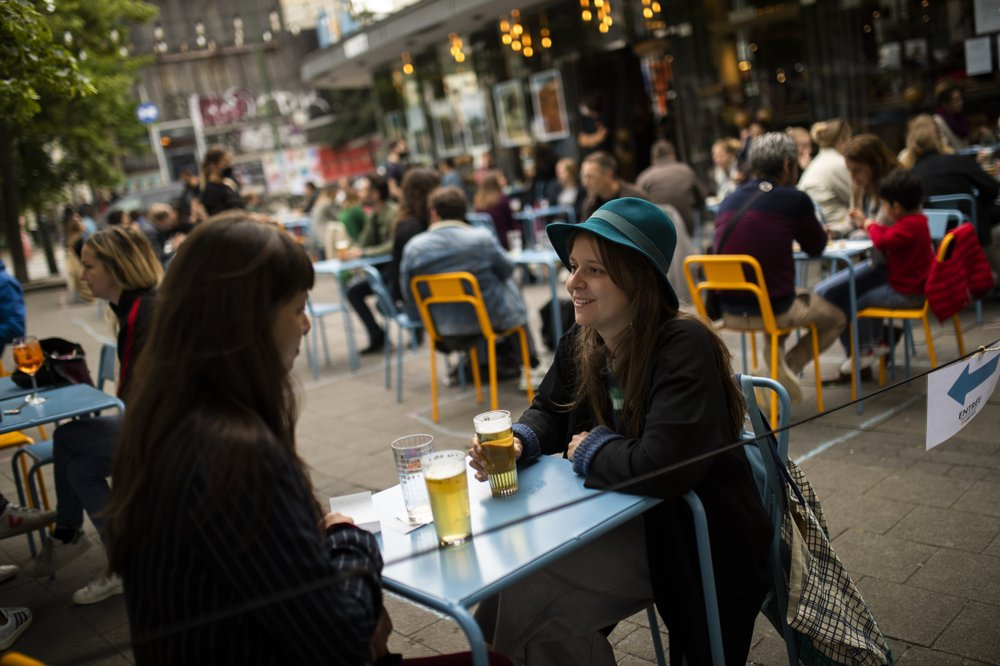 "Customers drink beers at the terrace of the Bar du Matin restaurant in Brussels on June 10, 2020. Alex Van Tuijn, co-owner of four cafes in Brussels, has found that staying in business during a pandemic can mean sacrificing some of the very things a company is known for. His Bar du Matin, a stalwart in the nightlife in the Belgian capital city, is no longer serving breakfast and lunch despite the fact ""matin"" is French for ""morning."" (AP)"