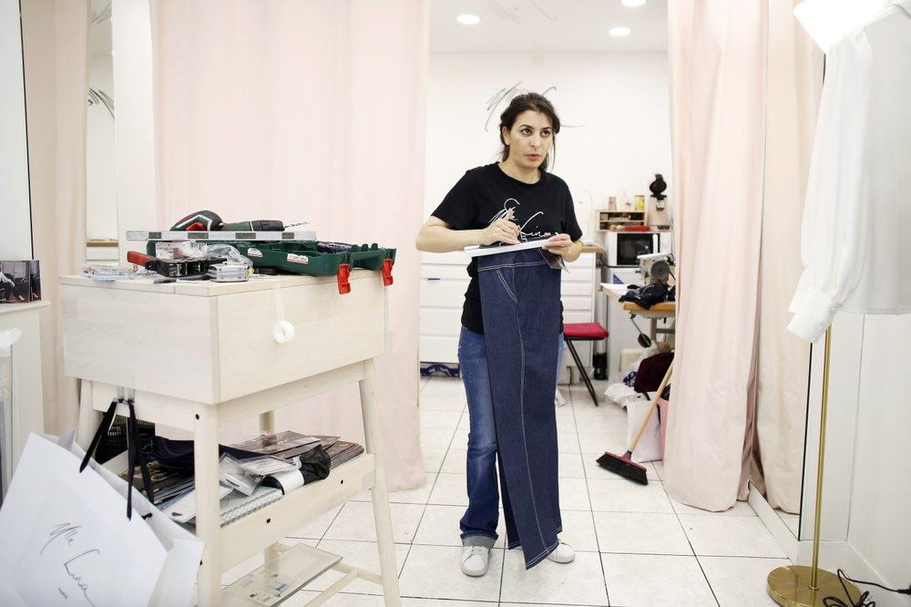 Dressmaker Lina Mokrane puts a trouser on a clothes rail during the new arrangement of her shop in Paris on Wednesday, June 17, 2020. Mokrane spent France's two-month shutdown trying to come up with ideas for keeping her Paris boutique going, knowing that when she reopened, established customers likely wouldn't be shopping. She has come up with a series of plans, beginning with an open house this weekend to bring in people from the neighborhood. (AP)