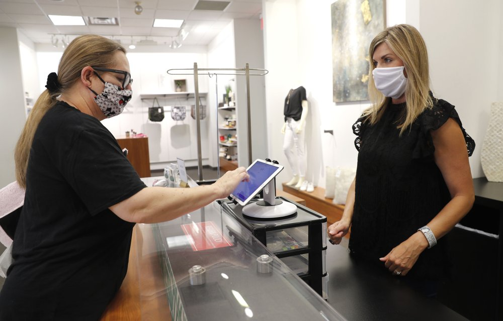 Monique Kursar, left, completes a purchase with Amy Witt, owner of the Velvet Window, in Dallas, May 13, 2020. For small retailers across the country, the coronavirus outbreak has turned an already challenging business environment into never-ending uncertainty. Witt might have 20 customers on a good day in her women's clothing store, and then none the next. (AP)