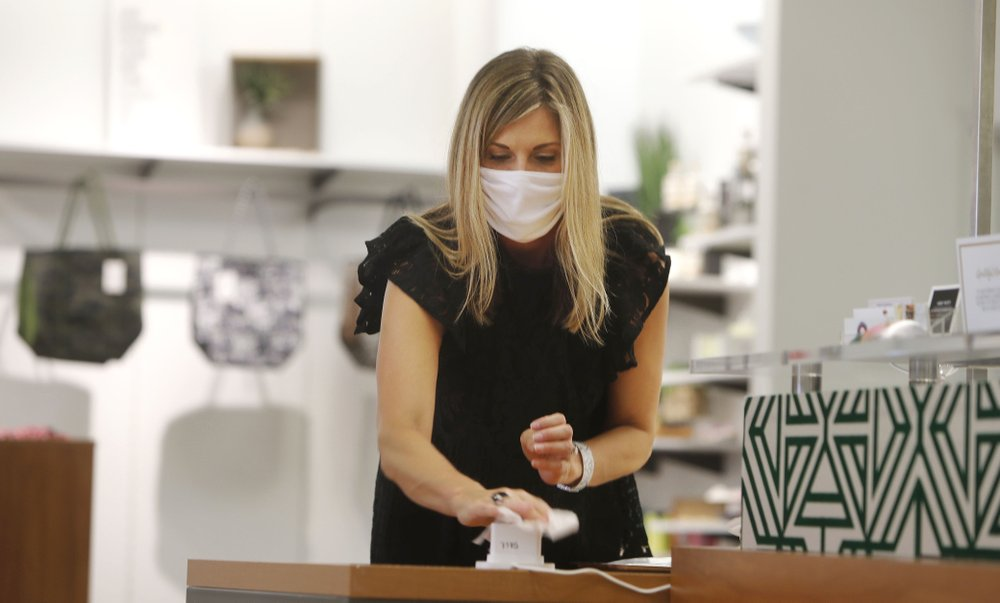 Amy Witt, owner of the Velvet Window, wipes a credit card reader after completing a sale with a customer at her store, in Dallas, May 13, 2020. (AP)