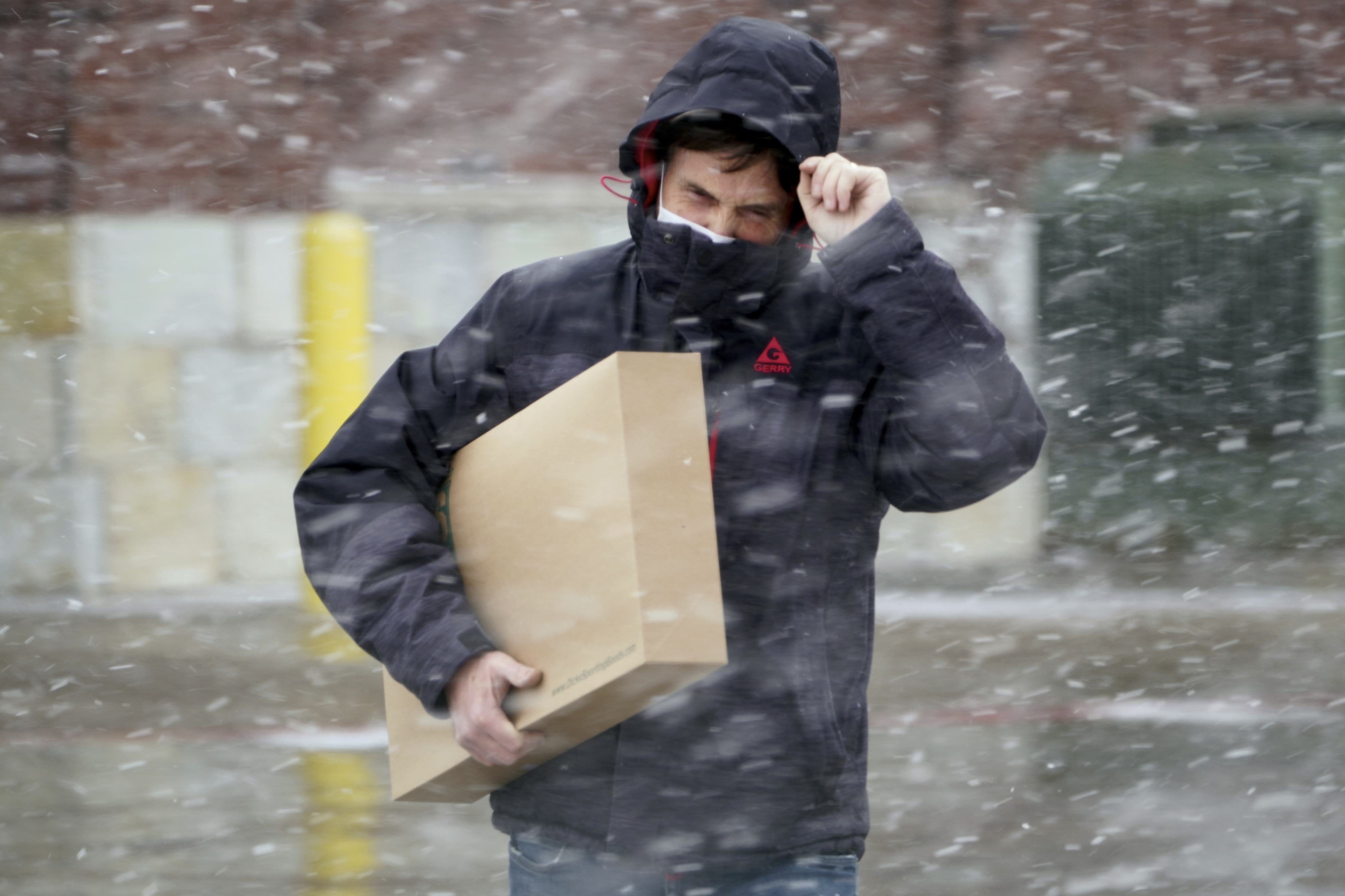A shopper carries a box as he walks to his vehicle in blowing snow in Omaha., Wednesday, Dec. 23, 2020. Retailers saw a mixed bag in 2020 due to the pandemic. Many smaller stores struggled, banking on the holiday shopping season, while big box stores remained open and emphasized curbside pickup and delivery. Online retailers like Amazon grew their market share, too. (AP)