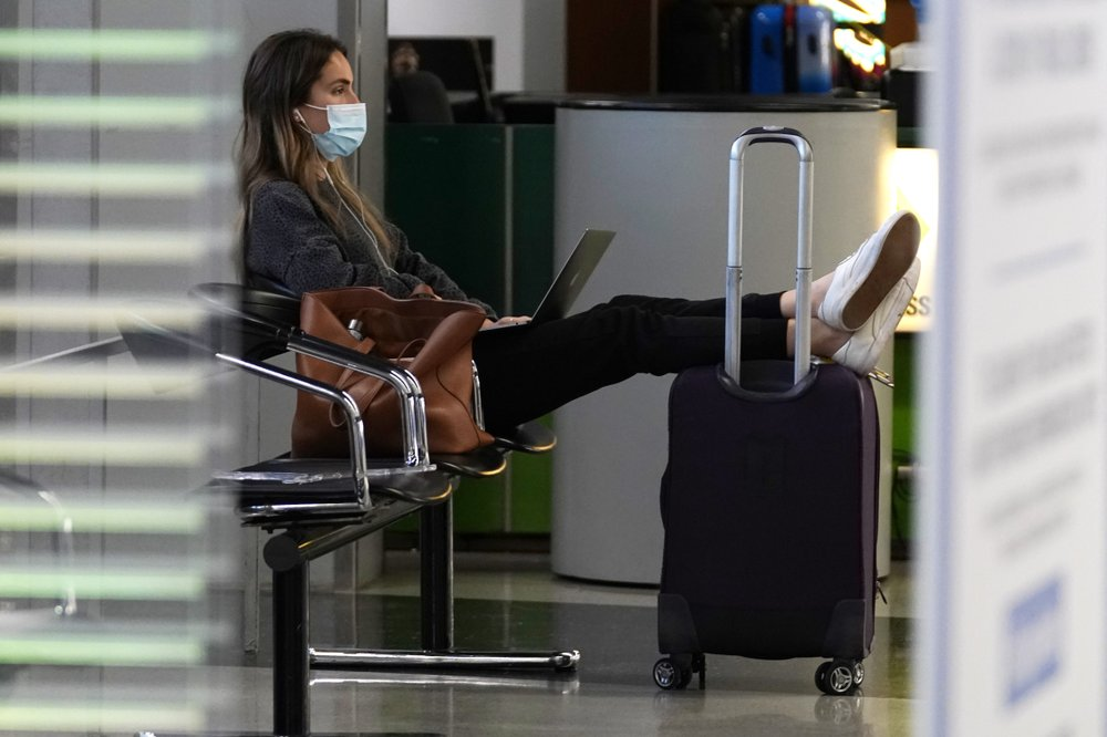 A traveler wears a mask as she waits for her flight in Terminal 3 at O'Hare International Airport in Chicago, Sunday, Nov. 29, 2020. Wall Street recovered after March, even though Main Street is still struggling. As few people traveled, the airline industry needed billions of dollars in aid from the government and is still threatening to lay off workers. (AP)