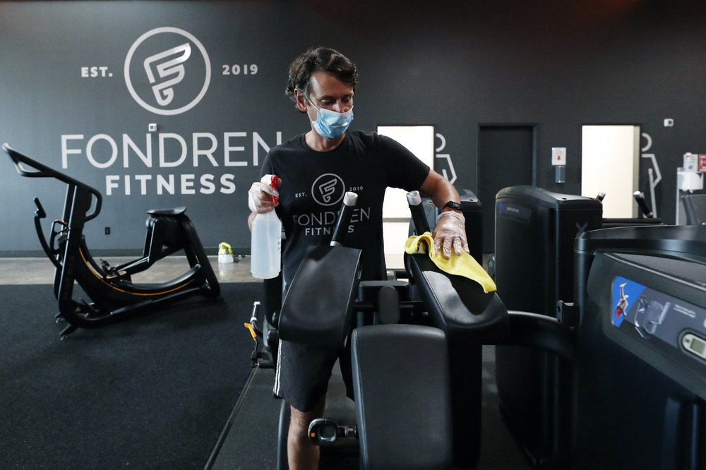 Terry Sullivan, general manager of Fondren Fitness sanitizes a workout machine in Jackson, Miss., May 14, 2020. Fitness regimens shifted from the gym to the home in a big way during 2020. Interactive fitness bike maker Peloton was one of the biggest winners of the workout-from-home trend as gyms did not fare so well as people avoided crowds. (AP)