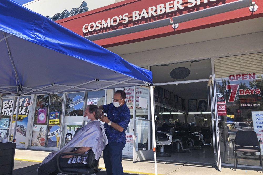 A customer of Cosmo's Barber Shop receives a haircut in the parking lot in front of the shop in Pleasanton, Calif., July 22, 2020. Efforts to mitigate the coronavirus had a severe toll on many small businesses. Restaurants, hair salons, event planners and other businesses that rely on people being in close proximity were hard-hit, as were those tied to tourism. (AP)