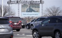 Rev. Greg Griffith, lead pastor at King of Kings church in Omaha, is seen on a giant screen during a drive-in Palm Sunday service, Sunday, April 5, 2020. Vehicles were parked to observe social distancing and worshippers were asked to stay in their cars and not roll down windows due to the coronavirus outbreak. (AP Photo/Nati Harnik)