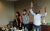 """Omaha Bar Association Executive Director Dave Sommers, center, imitating a zebra, raises Steve Hogan's arm in victory over a disbelieving Mallory Hughes in the second round of the """"Battle of the Guest BARtenders"""" at Berry Law's offices, July 14, 2021. (David Golbitz/Daily Record)"""