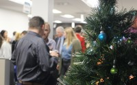 Greater Omaha Chamber members enjoy food, drink and each other's company by a Christmas tree set up in the chamber offices in downtown Omaha during the Member Appreciation Holiday Open House on Thursday, Dec. 5, 2019. (Photo by Scott Stewart)