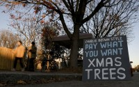 Pedestrians walk by Frank Pichel's tree lot, Sunday, Dec. 6, 2020, in Richmond, Va. A Virginia man has found a way to use Charlie Brown-style Christmas trees to benefit a middle school that provides scholarships for students from an impoverished area. (AP)