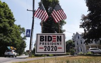 A car passes a yard displaying a campaign sign for Democratic presidential candidate Joe Biden in North Hampton, New Hampshire, June 23, 2020. The coronavirus pandemic isn't going away anytime soon, but campaigns are still forging ahead with in-person organizing. The pandemic upended elections this year, forcing campaigns to shift their organizing activities almost entirely online and compelling both parties to reconfigure their conventions.(AP)