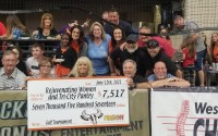 Members of the Sarpy County Chamber Fusion group and their sponsors pose for a photo with a check for the Tri-City Food Pantry and Rejuvenating Women at an Omaha Beef game at Ralston Arena, June 12, 2021. (Sarpy County Chamber Fusion)