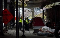 Washington, D.C., officials confer under a railroad overpass on L Street NE, about eight blocks from the U.S. Capitol, before garbage trucks and front loaders remove the homeless encampment there, March 3, 2020. (Susannah Outhier/University of Maryland via AP)