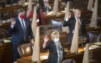 Newly elected and re-elected state senators, including Sen. Lou Ann Linehan, center, take the oath of office during the first day of the 2021 legislative session on Wednesday, Jan. 6, 2021, at Nebraska State Capitol. (Justin Wan/Lincoln Journal Star via AP)