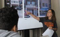 Jennifer Honebrink, an architect at Alley Poyner Macchietto, points out how a historical building was restored to Making Invisible Histories Visible students visiting the architectural firm on July 25, 2019. (Photo by Scott Stewart)