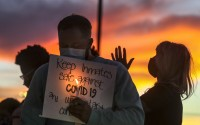 Family members of inmates incarcerated in the Utah Department of Corrections' prison system hold candles and say a prayer following a rally outside the Department of Corrections office in Draper, Utah, Oct. 13, 2020. (Steve Griffin/Deseret News via AP)
