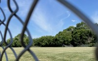 The city-owned soccer fields on Serum Road are being sold to a developer to be transformed into storage units. The fields are shown through a chain link fence Tuesday, June 22, 2021. (Molly Ashford/Daily Record)
