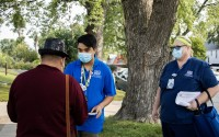Eddie Nuñez and Mary McConnaughey, employees of One World Community Health Centers, talk to a passerby as they go door-to-door in a South Omaha neighborhood, offering residents the COVID-19 vaccine. (Jazari Kual/Flatwater Free Press)