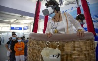 A woman wearing a face mask takes a virtual reality ride in a hot air balloon at the China International Fair for Trade in Services  in Beijing, Sept. 5, 2020. (AP)