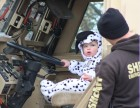 Axten Leclair, 16 months, dressed as a Dalmatian, gives a skeptical look to a Douglas County Sheriff's Office deputy while sitting inside an MRAP vehicle during a Halloween-themed open house and trunk-or-treat at the Douglas County Sheriff's Office, 3601 N. 156th St., on Saturday, Oct. 27, 2019. (Photo by Scott Stewart)