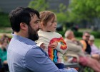 David Martin and 22-month-old Yvette watch musicians perform at Turner Park in Midtown Crossing during Legal Aid of Nebraska's Omaha Gives celebration on Wednesday, May 23, 2019. (Photo by Scott Stewart)